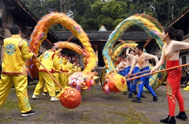Volunteers perform dragon and lion dance for villagers in SW China's Sichuan
